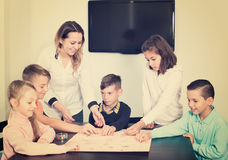 Donna e bambini che si siedono alla tavola con il gioco da tavolo Fotografia Stock Libera da Diritti