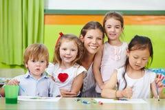 Donna e bambini felici della scuola materna Immagine Stock