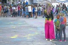Donna e bambini nella pittura al festival dei colori immagini stock