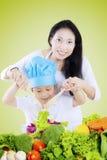 Donna e bambino che mescolano insalata Fotografia Stock Libera da Diritti