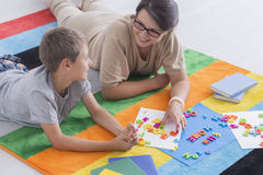 Donna e bambino che risolvono puzzle Fotografie Stock