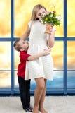 Donna e bambino con il mazzo dei fiori Concetto di festa della famiglia della primavera Giorno del `s delle donne Fotografia Stock Libera da Diritti