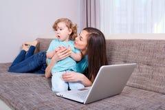 Donna e bambino felici della famiglia con un computer portatile sul sofà a casa Immagini Stock Libere da Diritti