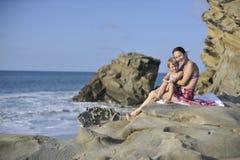 Donna e bambino sulla spiaggia rocciosa Immagini Stock Libere da Diritti
