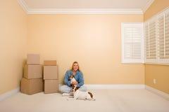 Donna e cani con le caselle commoventi nella sala sul pavimento Fotografia Stock