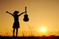 Donna e chitarra felici con la siluetta di tramonto Fotografia Stock