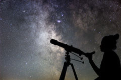 Donna e cielo notturno Sorveglianza della donna delle stelle con il telescopio Immagine Stock Libera da Diritti