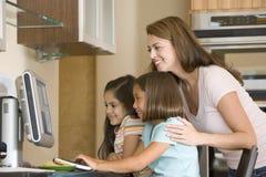 Donna e due ragazze in cucina con il calcolatore Fotografia Stock Libera da Diritti