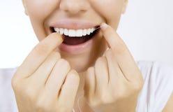 Donna e filo di seta dei denti fotografia stock