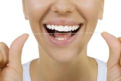Donna e filo di seta dei denti immagine stock
