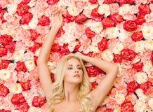 Donna e fondo in pieno delle rose fotografie stock
