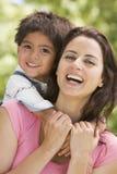 Donna e giovane ragazzo che abbracciano all'aperto sorridere immagini stock libere da diritti