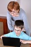 Donna e giovane ragazzo con il computer portatile Immagini Stock Libere da Diritti
