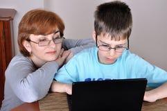 Donna e giovane ragazzo con il computer portatile Fotografie Stock Libere da Diritti