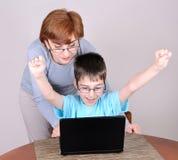 Donna e giovane ragazzo con il computer portatile Fotografia Stock Libera da Diritti