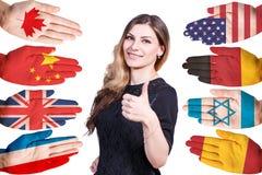 Donna e molte mani con differenti bandiere Immagini Stock Libere da Diritti