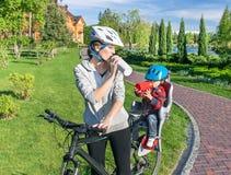 Donna e neonato caucasici su una bicicletta Fotografia Stock
