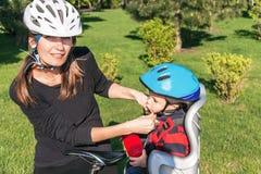 Donna e neonato caucasici su una bicicletta con i caschi di ciclismo Fotografie Stock