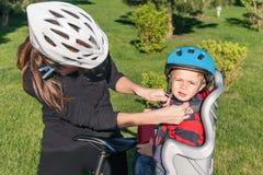 Donna e neonato caucasici su una bicicletta con i caschi di ciclismo Fotografia Stock