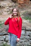 Donna e parte anteriore del poziruye degli abiti di rosso della macchina fotografica sui precedenti Fotografia Stock Libera da Diritti