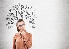 Donna e punti interrogativi di pensiero su calcestruzzo Immagini Stock