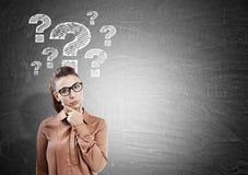 Donna e punti interrogativi di pensiero sulla lavagna Immagini Stock