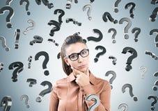 Donna e punti interrogativi di pensiero sulla parete grigia Fotografia Stock Libera da Diritti