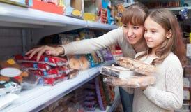 Donna e ragazza che acquistano i dolci al supermercato Fotografia Stock