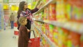 Donna e ragazza che scelgono i prodotti nel centro commerciale Mamma e figlia dopo avere messo alcune merci nella passeggiata ros stock footage