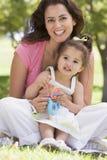 Donna e ragazza che si siedono con sorridere del giocattolo Immagine Stock