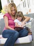 Donna e ragazza che si siedono sul libro di lettura del patio Immagine Stock