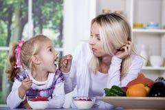 Donna e ragazza con la ciotola del yogurt Immagine Stock