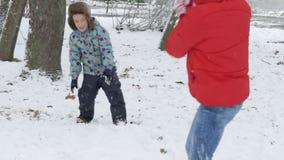 Donna e ragazzo che giocano le palle di neve nella neve archivi video
