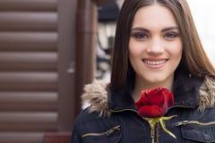 Donna e rosa rossa castane abbastanza giovani Immagine Stock