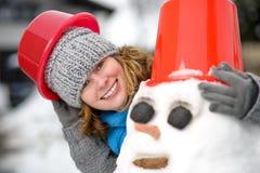 Donna e un pupazzo di neve fotografia stock