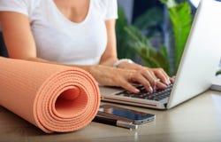 Donna e una stuoia di esercizio in un fondo dell'ufficio immagine stock