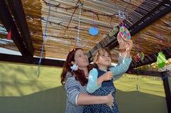 Donna ebrea e bambino che decorano la loro famiglia Sukkah Fotografia Stock