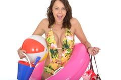 Donna eccitata portando un vestito di nuotata sugli elementi di trasporto della spiaggia di festa Immagine Stock