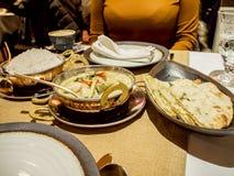 Donna ed alimento indiano in un ristorante immagine stock
