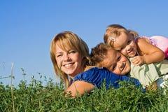 Donna ed i suoi bambini che giocano all'aperto Immagini Stock Libere da Diritti