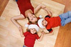 Donna ed i suoi bambini sul pavimento a natale Immagine Stock Libera da Diritti