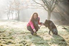 Donna ed il suo allungamento del cane all'aperto Ragazza di forma fisica ed il suo animale domestico che risolvono insieme Fotografia Stock Libera da Diritti