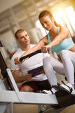 Donna ed istruttore che risolvono sulla macchina di esercizio in palestra fotografia stock