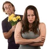 Donna ed uomo arrabbiati con i fiori immagine stock