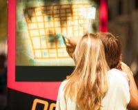Donna ed uomo che guardano una mappa sulla via fotografia stock libera da diritti