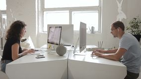 Donna ed uomo che lavorano al computer che si siede nel centro di affari all'interno video d archivio