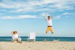 Donna ed uomo che riposano sulla spiaggia Fotografia Stock