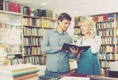Donna ed uomo con i libri ed il telefono Fotografie Stock Libere da Diritti