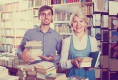 Donna ed uomo con i libri in negozio Fotografie Stock