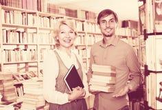 Donna ed uomo con i libri in negozio Immagine Stock